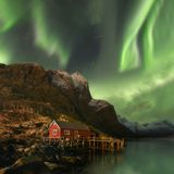 Northern lights in Lofoten islands, Norway. Green Aurora borealis. Starry sky with polar lights. Night winter landscape in night. royalty free stock photos