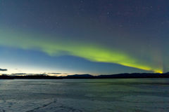 Northern Lights and morning dawn over frozen lake Royalty Free Stock Images