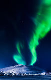 Northern lights in the mountains house of Svalbard, Longyearbyen city, Spitsbergen, Norway wallpaper. The polar Northern lights in the mountains house of Royalty Free Stock Photo