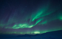 The Northern lights in the mountains of Svalbard, Longyearbyen, Spitsbergen, Norway wallpaper. The polar Northern lights in the mountains of Svalbard royalty free stock images