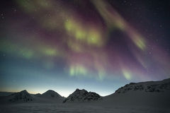 Northern Lights over the Arctic mountains - Spitsbergen, Svalbard. Natural phenomenon of Northern Lights (Aurora Borealis) related to the earth's magnetic field royalty free stock photos