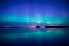 Northern lights. Over calm lake (Aurora borealis) in Sweden Stock Photos