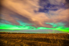 Northern lights over farm field with dramatic cloudscape Stock Photo