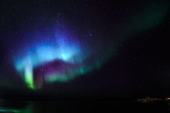 Northern lights over the fjord, view from the old harbor Royalty Free Stock Photography