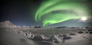 Northern lights over the frozen fjord - PANORAMA. Arctic winter landscape with northern lights - Spitsbergen, Svalbard Stock Images