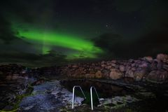 GRETTISLAUG Campsite on Iceland, northern lights. Northern lights over the hot spring bath in the GRETTISLAUG Campsite on Iceland royalty free stock photo