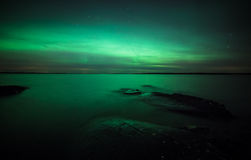 Northern lights over lake in finland Royalty Free Stock Images