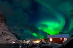 Northern Lights over Norwegian Houses. Norway. Lofoten. The Island Hamnøy. Winter night. Northern lights Royalty Free Stock Photo