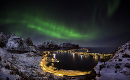 Northern lights over Reine, Norway. A man looking at the northern lights over Reine, Lofoten islands, Norway
