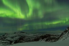Northern lights over snow covered mountains at distant Norway co Stock Photos