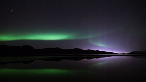 Northern Lights & the Peace Tower. The Northern Lights dancing over lake Kleifarvatn in Iceland. In the distance Yoko Onos Imagine Peace Tower shines into the stock images