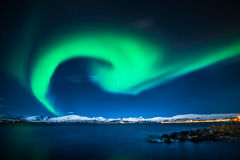 Northern lights. This photo is taken in Tromso in Norway. The Northern lights came from a mountain, shining cross the sky Stock Image