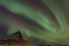 Northern Lights and satellite trail over Kirkjufell mountain Stock Images