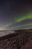 Northern Lights by the sea. Northern lights or Aurora Borealis dancing in the sky below the shore in Iceland stock photos