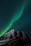 Northern Lights & Shooting Stars. Northern lights with a shooting star invading the skies above a lit up rock formations Stock Photos