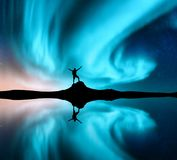 Northern lights and silhouette of a man with raised up arms stock photography