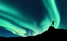 Northern lights and silhouette of standing happy man. Aurora. Northern lights and silhouette of standing man with raised up arms on the mountain peak in Norway stock photos
