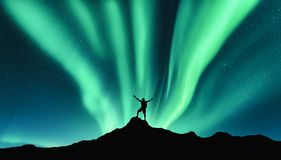 Northern lights and silhouette of standing happy man. Aurora royalty free stock photo