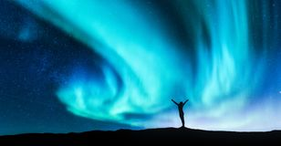 Northern lights and silhouette of a woman with raised up arms. Northern lights and silhouette of standing woman with raised up arms on the hill in Norway. Aurora royalty free stock photos
