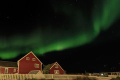Northern lights and starlight sky over two red living houses, Nu Royalty Free Stock Photography