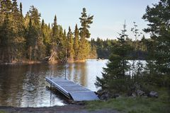 Northern Minnesota lake with dock and fishermen in the distance. A typical northern Minnesota lake with a dock and fishermen in the distance royalty free stock photos