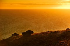 Northern moai. Landscape with a silhouette of a fancy stone at sunset and the passing ship Royalty Free Stock Photo