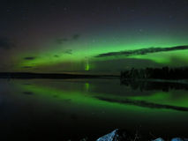 Northern Reflections ... Dance of the Northern Lights. The Aurora Borealis shines, shimmers and dances its reflection over the calm waters of a northern Stock Image