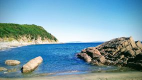 Northern seacoast. A seacoast, rocks and mountains covered by taiga forest at the Kongoli Spring beach, Okhotsk sea, near Magadan and Ola county - former Stalin` royalty free stock photos