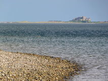 Northumberland beach. Picturesque stoney beach as tide goes out, gentle waves, blue skies, northumberland coastline. bamburgh castle in distance Stock Photos