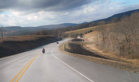 Northwest Arkansas Ozark Mountain Highway. Winter road with dark skies on a highway in the Ozark Mountains includes a car and a motorcycle on a mostly empty road Royalty Free Stock Images
