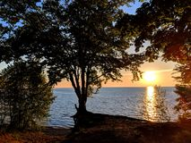 Northwoods Lake Superior Sunsest. Beautiful Lake Superior sunset framed by dense forest cover of Northwoods Michigan stock images