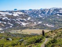 Noruega - uma menina com uma trouxa de caminhada no trhough da fuga um plat? das montanhas imagens de stock royalty free