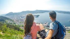 Noruega - un par sittting en una roca, con la opini?n sobre Bergen imágenes de archivo libres de regalías