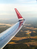 Norvegian Airlines airplane wing flying above the Scandinavian Royalty Free Stock Images