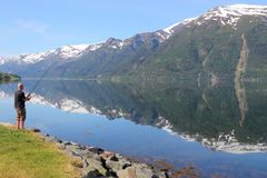 Norway angling. HARDANGER FIORD, NORWAY - JULY 17, 2015: Man enjoys angling at Sorfjord part of Hardanger Fiord, Norway. Foreign tourists spent some 5 million Royalty Free Stock Photography