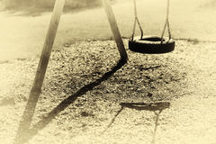 Norway children swing from tire sepia background Royalty Free Stock Photo
