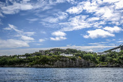 Norway coast with charming cottages in the background, summer, s. Unny sky with clouds Royalty Free Stock Image