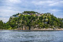 Norway coast with charming cottages in the background, summer, s. Unny sky with clouds Royalty Free Stock Images