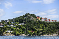 Norway coast with charming cottages in the background, summer, s. Unny sky with clouds Royalty Free Stock Photos