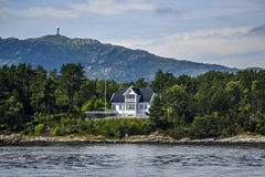 Norway coast with charming cottages in the background, summer, s. Unny sky with clouds Stock Image