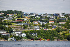 Norway coast with charming cottages in the background, summer, s. Unny sky with clouds Stock Photo