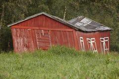 norway Countr abandonné et incurvé rustique en bois rouge de maison de ferme Image libre de droits