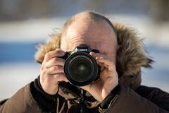 Norway, february 3, 2018: A male photographer in winter clothing is holding a Canon camera with the Canon 24-70mm 2,8 L. A photographer is holding a Canon camera Royalty Free Stock Photography
