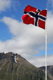 Norway flag. Waving in front of cloudy and maountain background stock image