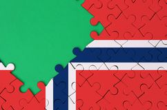 Norway flag is depicted on a completed jigsaw puzzle with free green copy space on the left side.  stock images