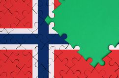 Norway flag is depicted on a completed jigsaw puzzle with free green copy space on the right side.  royalty free stock photography