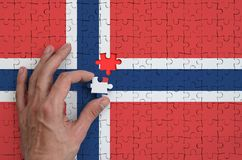 Norway flag is depicted on a puzzle, which the man`s hand completes to fold.  royalty free stock photo