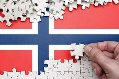 Norway flag is depicted on a table on which the human hand folds a puzzle of white color.  royalty free stock images
