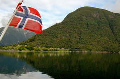 Norway flag of a ferryboat sailing in a fjord. On the left norway flag of a ferryboat sailing in a fjord royalty free stock photo