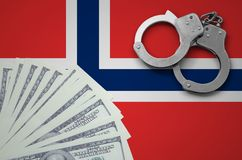 Norway flag with handcuffs and a bundle of dollars. The concept of illegal banking operations in US currency.  stock photos